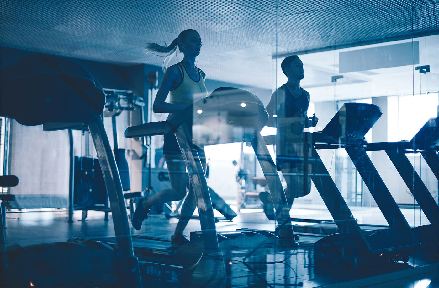Woman and man running on treadmill